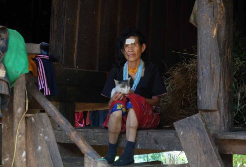 A Karen woman and her cat at the steps of her hut